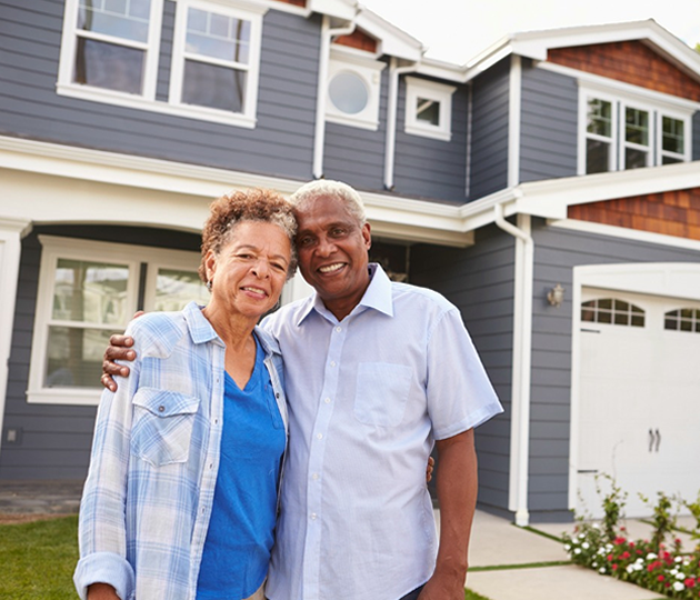 elderly couple in front of home